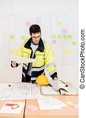 Construction Worker Turning Pages While Holding Blueprint