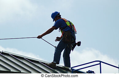 Construction worker using a rope for safety on a roof of a office building