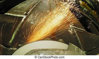 Construction worker using an angle grinder producing a lot of sparks.