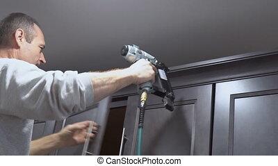 Construction worker using brad nail air gun to Crown...