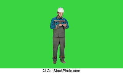 Construction worker using cell phone to send message on a Green Screen, Chroma Key.