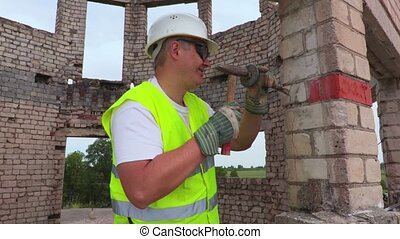 Construction worker using chisel and hammer