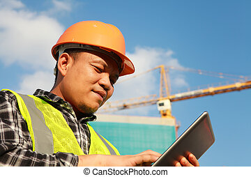 construction worker using digital tablet with crane on the background