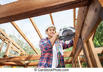 Construction Worker Using Electric Saw On Wooden Frame At Site