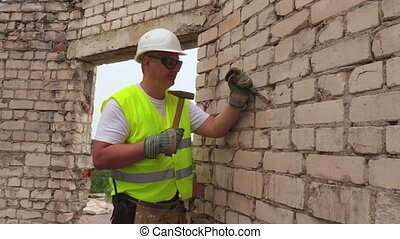Construction worker using hammer and chisel