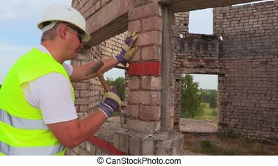 Construction worker using hammer near wall