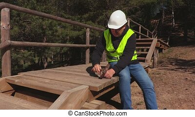 Construction worker using hammer on wooden stairs