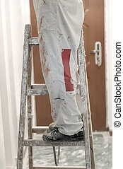 Construction worker using ladder for working on home renovations