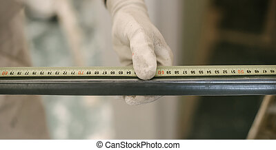 Construction worker using measuring tape