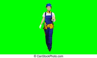 Construction worker wearing a helmet carries three wooden boards. Green screen