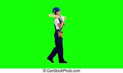 Construction worker wearing a helmet carries three wooden boards. Green screen. Side view