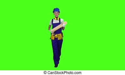 Construction worker wearing a helmet carries three wooden boards. Green screen. Slow motion