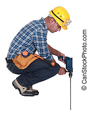 Construction worker with a masonry drill