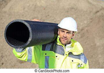 Construction worker with a pipe on his shoulder