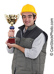 Construction worker with a trophy