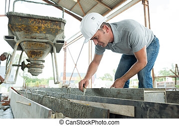 construction worker with cement in the cement trolley