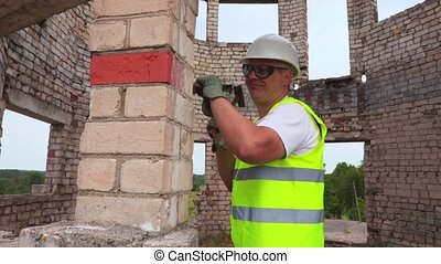 Construction worker with chisel and hammer near brick wall