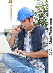 Construction worker with computer and phone