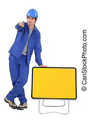Construction worker with yellow road sign