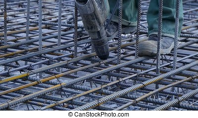 Construction worker. Worker in the construction site making reinforcement metal framework for concrete pouring