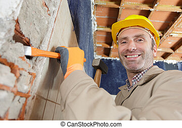 construction worker working with hammer and chisel