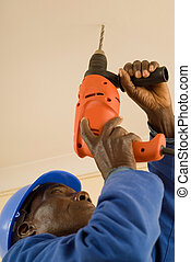 Construction Worker Working with Power Tool - African...