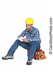 Construction worker writing in a notebook