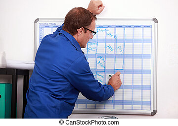 Construction worker writing in deadlines on a calender