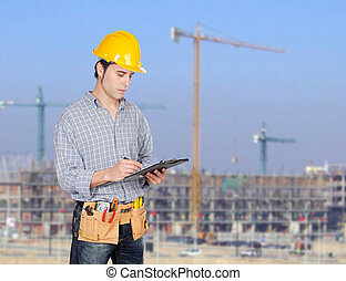 Construction worker writing paperwork with a construction...