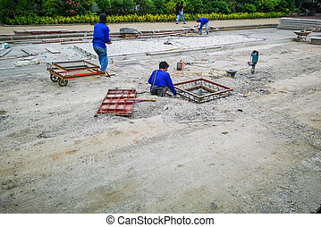 Construction workers are making pipes on the road.