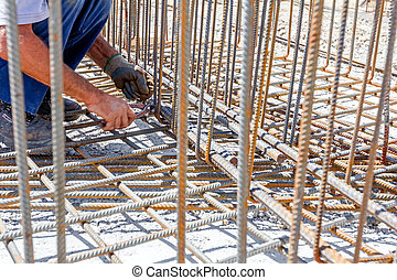 Construction workers binding rebar for reinforce concrete column at the building site.