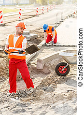 Construction workers building new road - Image of...