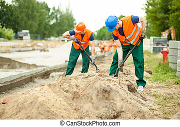Construction workers digging - Image of construction workers...