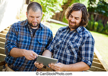 Construction Workers Discussing Project On Digital Tablet