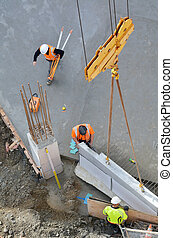 Construction workers guides a structural precast concrete into place