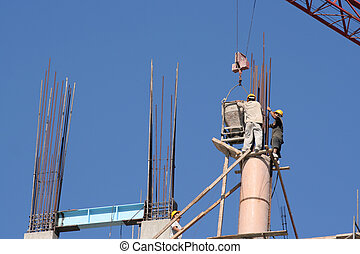 Construction - Workers in Mexico pour concrete collumns for...