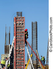 Construction workers installing formwork on site