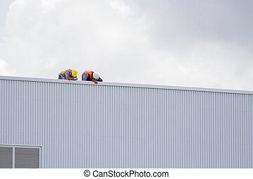 Construction workers on the roof of the building.