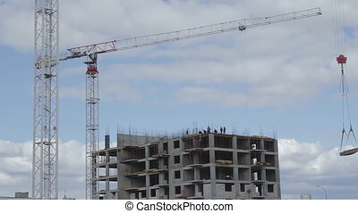 Construction workers on the roof of the new building, crane