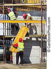 Construction workers placing formworks - Team work at ...