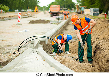Construction workers renovating road in a big city