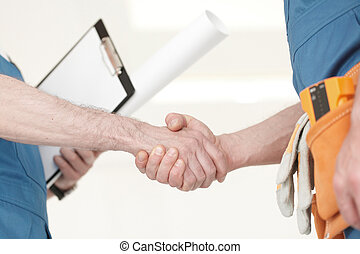 Construction workers shaking hand
