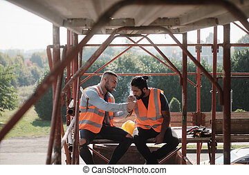 Construction Workers Smoking Cigarette And Talking On Break