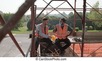Construction Workers Smoking Cigarette Relaxing And Talking On Break