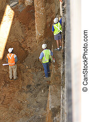 Construction workers - Three construction workers, one...