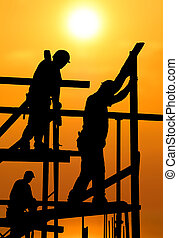 Construction workers under a hot blazing sun - Silhouette of...