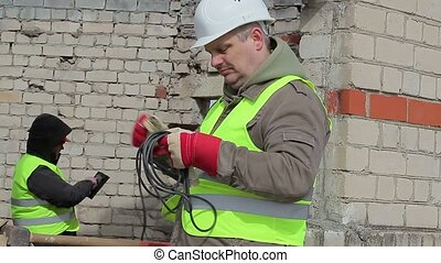 Construction workers with extension cord and tablet PC