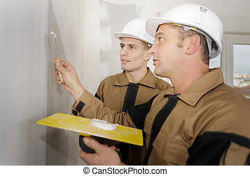 construction workers with wall plastering tools renovating apartment house