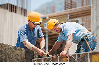 Construction workers working on cement formwork frames -...