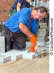 construtor, deitando, pedras pavimentando, com, seu, equipe